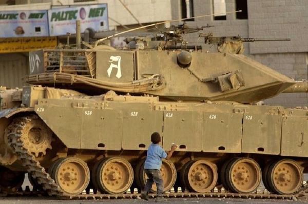 Palestinian faces Israeli tank