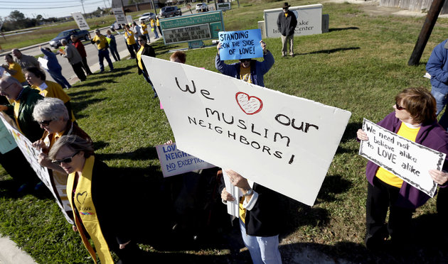 Paula Criswell, center, holds a sign as she joins others in a rally to show support for Muslim members of the community near the Clear Lake Islamic Center in Webster, Texas on Friday, Dec. 4, 2015. Members of several Unitarian Universalist churches and the Unitarian Voices for Justice group showed their support as attendees made their way to the center for Friday prayers. Organizers said the rally was scheduled prior to Wednesday's mass shooting in San Bernardino, Calif. (AP Photo/David J. Phillip)